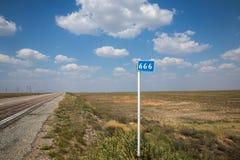 Kilometerkennzeichen auf Hintergrund der Sommerstraße und des bewölkten Himmels Stockbilder
