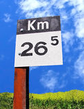 Kilometers sign post vertical. Kilometers sign post with yellow flowers and blue sky background Stock Images