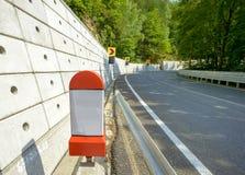 Kilometersteinbeitrag auf dem Straßenrand Stockfotografie