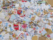 Kiloware. Large pile of mostly British used postage stamps. WREXHAM, UK - MARCH 15, 2015: Kiloware, a large pile of used postage stamps torn from envelopes Royalty Free Stock Image