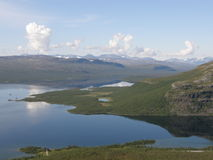 Kilpisjarvi lake som omges av kullar och berg Royaltyfria Bilder