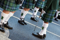 Kilts and Ghillie Brogues. Legs of traditional Irish bagpipes players wearing black shoes (Ghillie brogues), intricate white woollen socks and pleated kilt Stock Images