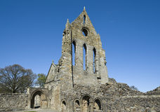 Kilwinning Abbey. View of part of the remains of Kilwinning Abbey showing the towering gable wall of the south transept, arched doorway, portal to slype, and Royalty Free Stock Photography