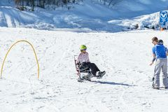 KIMBERLEY, CANADA - MARCH 19, 2019: handicapped person riding a mono ski Vancouver Adaptive Snow Sports. Active activity alpine athlete disability disabled royalty free stock images