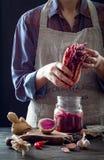 Kimchi капусты в стеклянном опарнике Женщина подготавливая пурпурное kimchi редиски капусты и арбуза Заквашенная и вегетарианская стоковая фотография