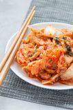 Kimchi cabbage. Korean appetizer on white plate, vertical Royalty Free Stock Images