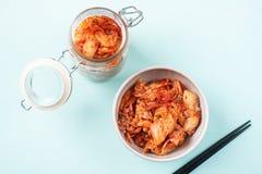 Kimchi kål i en bunke och en krus med pinnar royaltyfri bild