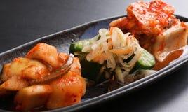 Kimchi sorterade med den jäste rädisan, och gurkan på svart plat Fotografering för Bildbyråer