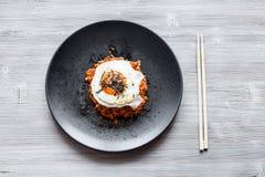 Kimchibokkeum bap op zwarte plaat en eetstokjes stock afbeelding