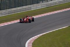 Kimi's car down track. Kimi Raikkonen taking corner at the Spa Francorchamps track in Belgium Royalty Free Stock Images