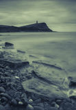 Kimmeridge Bay and Clavell Tower. Black and white portrait of the rocks of Kimmeridge Bay with Clavell Tower in the distance atop Hen Cliff Royalty Free Stock Photo