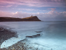 Kimmeridge Bay and Clavell Tower. Landscape at dawn of the rocks of Kimmeridge Bay with Clavell Tower in the distance atop Hen Cliff Stock Image