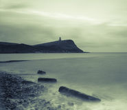 Kimmeridge Bay and Clavell Tower, Dorset, England. Black and white landscape of the rocks of Kimmeridge Bay with Clavell Tower in the distance atop Hen Cliff Stock Photos