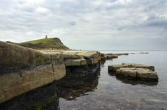 Kimmeridge Bay In Dorset. Kimmeridge Bay on Dorset's Jurassic coast, slate ledges revealed by a low tide and looking out towards Clavell's Tower on the nearby Royalty Free Stock Image