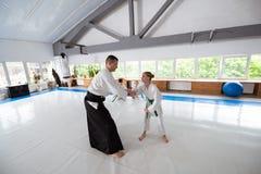 Kimono blanc de port de fille ayant le combat avec l'entraîneur images libres de droits