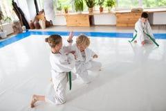 Kimono blanc de port de garçon et de fille ayant le combat tout en pratiquant photos stock
