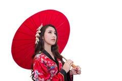 Kimono d'uso della bella giovane donna asiatica con l'ombrello rosso Fotografie Stock