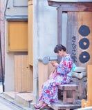 Kimono del desgaste de mujer joven que se sienta en banco de madera y que juega el teléfono móvil Imagenes de archivo