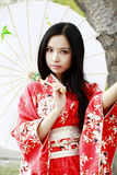 Kimono girl. Beautiful Asian girl in traditional kimono holding a umbrella under cherry tree Royalty Free Stock Images
