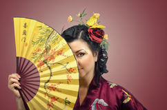 Kimono white woman hiding her face behind Asian fan Stock Photos
