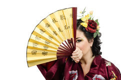 Kimono woman looking at you through the open fan Royalty Free Stock Images
