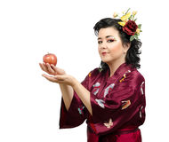 Kimono woman offering a red apple Stock Photography