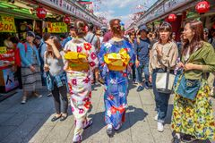 Kimono women in Nakamise-dori. Tokyo, Japan - April 19, 2017: women`s back in japanese kimonos walking in spring sakura on Nakamise-dori, a street with food and Royalty Free Stock Image
