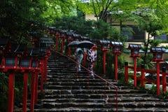 2 Kimonodamen kämpften durch Regen zum Maß Glauben Stockfotos