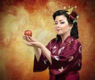 Kimonokvinna som fördjupa hennes armar med äpplet Arkivfoton