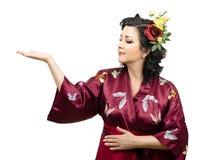 Kimonokvinna som fördjupa hennes högra arm med annonsutrymme Arkivfoto