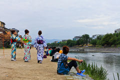 Kimonos in Kyoto. Japanese women in traditional kimono walk along the banks of the Kamo River in Kyoto. The riverbanks are popular to both locals and tourists as Stock Image