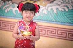 Kina flicka i klänninghälsningen för traditionell kines som rymmer en guld royaltyfria bilder