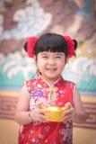 Kina flicka i klänninghälsningen för traditionell kines som rymmer en guld royaltyfri fotografi