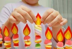 Kind übergibt das Setzen einer Papierflamme auf handgemachtes hanukah Stockfotografie