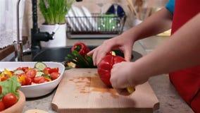 Kind übergibt den Schnitt eines roten bellpepper für einen Gemüsesalat stock video footage