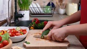 Kind übergibt die Anfänge, die eine Gurke für einen Salat schneiden stock footage