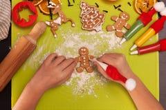 Kind übergibt die Herstellung von Lebkuchenplätzchenleuten - Draufsicht Lizenzfreies Stockbild