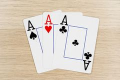 3 of a kind aces - casino playing poker cards. 3 of a kind aces - winning hand of gambling casino poker playing cards on a table royalty free stock photo