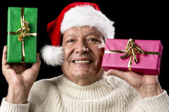 Kind Aged Gentleman With Red Cap Raising Two Gifts. Friendly old man with red Santa Claus hat and warm pullover. He is raising a green and a magenta wrapped Stock Photo