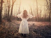 Kind allein im weißen Kleid im Holz lizenzfreie stockfotos