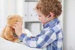 Kind Arts Checking de Hartslag van een Teddybeer Stock Fotografie