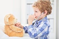 Kind Arts Checking de Hartslag van een Teddybeer Stock Afbeelding