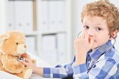 Kind Arts Checking de Hartslag van een Teddybeer Stock Afbeeldingen