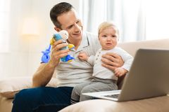 Kind attentive father showing a toy to his crying baby and smiling stock photos