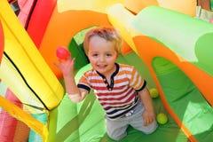 Kind auf aufblasbarem federnd Schloss Lizenzfreie Stockfotos