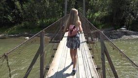 Kind auf Brücke in den Bergen, Kind, das in der Natur, Mädchen schaut einen Fluss, Strom wandert stock video footage