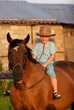 Kind auf braunem Pferd lizenzfreies stockfoto