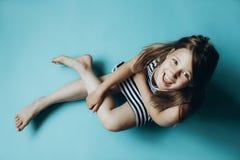 Kind auf dem einfachen blauen Hintergrund, der das Kamerasitzen betrachtet stockfotos