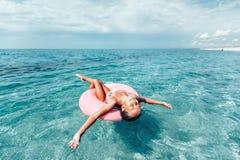 Kind auf dem lilo, das auf dem Strand sich entspannt stockfoto