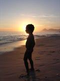 Kind auf dem Strand im Schattenbild Stockfotos